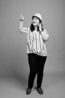 Ujęcie całego ciała dojrzałej, pięknej azjatyckiej bizneswoman jako inżyniera z telefonem