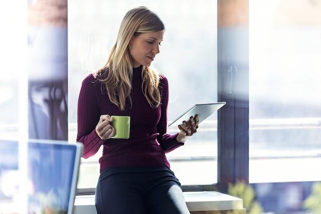 Ujęcie całkiem młoda kobieta biznesu za pomocą swojego cyfrowego tabletu i trzymając filiżankę kawy, siedząc przy oknie w biurze.