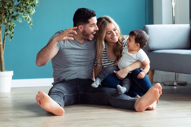 Ujęcie całkiem młodych rodziców bawiących się z synkiem siedząc na podłodze w domu.