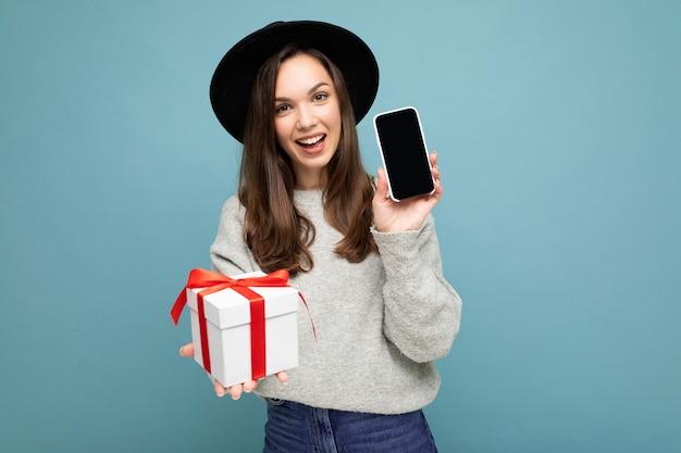 Ujęcie całkiem uśmiechnięta pozytywna młoda kobieta brunetka samodzielnie na niebieskim tle ściany noszenia