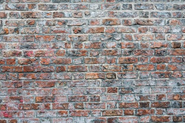 Ujęcie cementowanej ściany z czerwonej i brązowej cegły - idealne do tapet