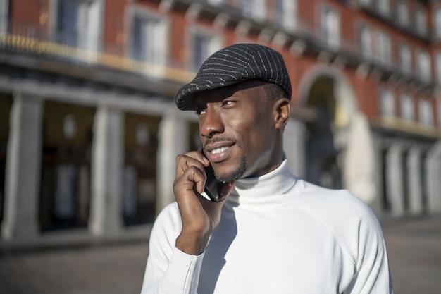 Ujęcie czarnego mężczyzny w kapeluszu i golfie rozmawiającego przez telefon