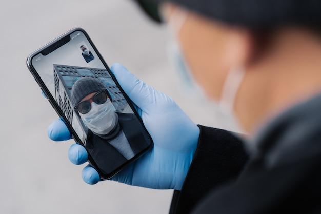Ujęcie człowieka odbywa wideokonferencję za pośrednictwem nowoczesnego smartfona, będąc z dala od ludzi podczas rozprzestrzeniania się koronawirusa, nosi maskę ochronną i gumowe rękawiczki podczas spacerów na zewnątrz w miejscu publicznym