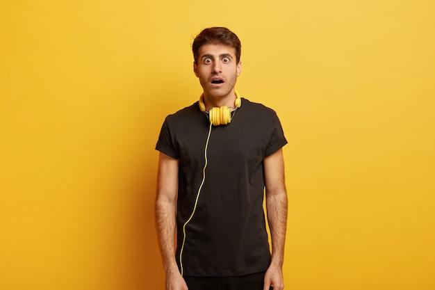 Ujęcie do połowy zdumionego młodego mężczyzny rasy kaukaskiej z szeroko otwartymi ustami, ubrany w czarny t shirt