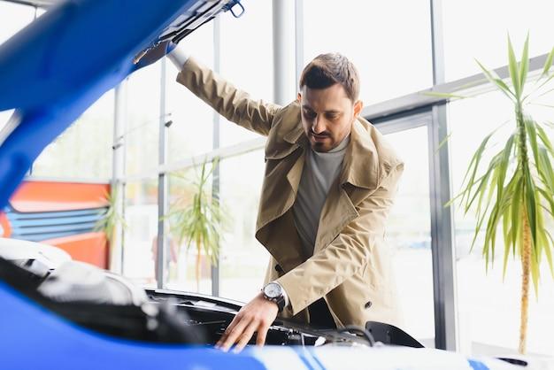 Ujęcie dojrzałego mężczyzny bada silnik nowego samochodu w salonie samochodowym patrząc pod maskę copyspace mechanika nowoczesna technologia jazdy pojazd konie mechaniczne samochodowe.