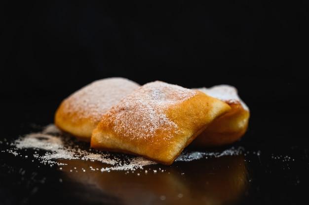 Ujęcie domowych ciast z słodkim proszkiem na czarnej ścianie