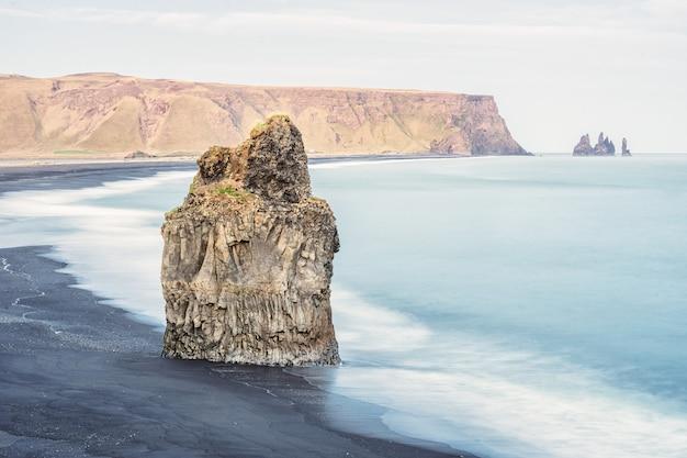 Ujęcie dużej skały w morzu, plaża reynisfjara w vik, islandia