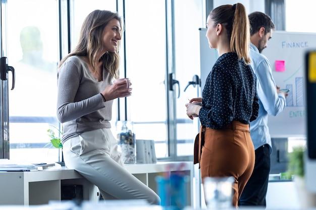Ujęcie dwóch biznesowych młodej kobiety picia kawy podczas przerwy na coworkingową przestrzeń.
