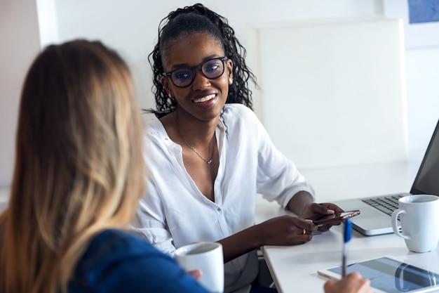 Ujęcie dwóch całkiem młodych kobiet biznesu używających razem swojego telefonu komórkowego podczas przerwy w biurze.