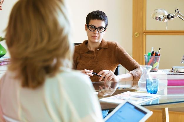 Ujęcie dwóch kobiet biznesu rozmawiających o pracy i wymieniających się pomysłami za pomocą cyfrowego tabletu w biurze.