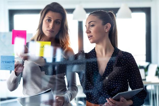 Ujęcie dwóch młodych kobiet biznesu pracujących razem na ścianie szklanej z naklejkami post it na coworking space.