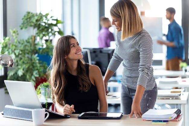 Ujęcie dwóch młodych kobiet biznesu pracujących razem z cyfrowym tabletem w nowoczesnym biurze startowym.