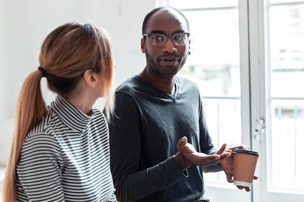 Ujęcie dwóch młodych ludzi biznesu rozmawiających i pijących kawę podczas przerwy w biurze.