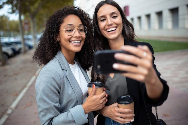 Ujęcie dwóch pięknych kobiet biznesu nawiązujących połączenie wideo za pomocą smartfona podczas picia kawy, spacerując po mieście.