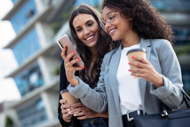 Ujęcie dwóch pięknych kobiet biznesu za pomocą smartfona podczas picia kawy, spacerując po mieście.