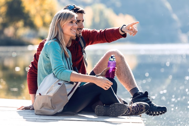 Ujęcie dwóch turystów siedzących podczas podróży, podczas gdy mężczyzna wskazuje coś w krajobrazie w jeziorze na górze.