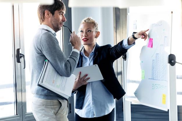 Ujęcie eleganckiej młodej bizneswoman wskazującej na tablicę i wyjaśniającej projekt swojemu koledze na coworkingu.