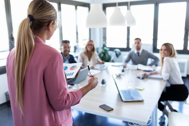 Ujęcie eleganckiej młodej bizneswoman wyjaśniającej nowy projekt swoim kolegom w miejscu coworkingowym. widok z tyłu.