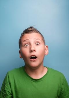 Ujęcie emocjonalnego uroczego chłopca zakrywającego głowę ręką będącą zmęczoną bólem głowy pokazującym prawdziwe emocje