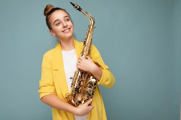Ujęcie fascynujące szczęśliwa uśmiechnięta brunetka mała nastolatka ubrana w modną żółtą kurtkę stojącą na białym tle nad niebieskim tle ściany trzymającej saksofon patrząc z boku. skopiuj miejsce