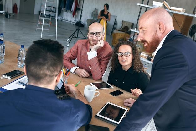 Ujęcie grupy młodych profesjonalistów po spotkaniu. różnorodna grupa młodych projektantów uśmiechających się podczas spotkania w biurze.