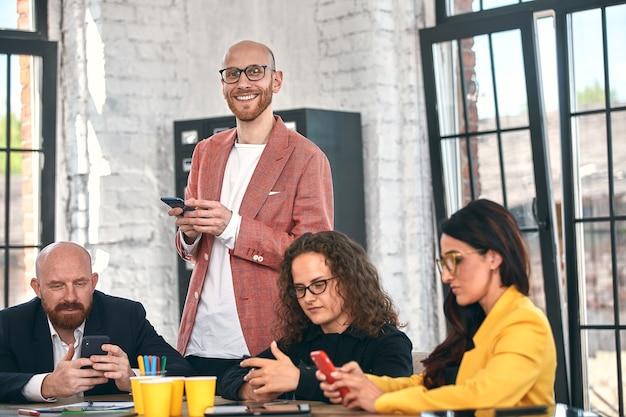 Ujęcie grupy młodych przedsiębiorców o spotkaniu zróżnicowana grupa młodych projektantów uśmiecha się podczas spotkania w biurze.