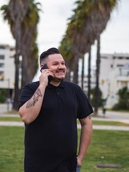Ujęcie kaukaskiego mężczyzny z hiszpanii rozmawiającego przez telefon na ulicy