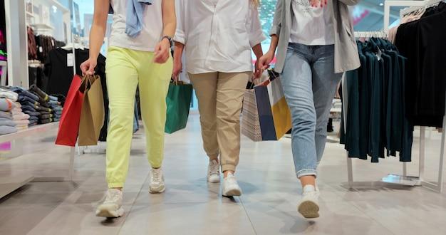 Ujęcie kobiece nogi idąc przez centrum handlowe w kolorowe ubrania. koncepcja życia młodzieży, przyjaźni i konsumpcjonizmu. zakupy po kwarantannie.