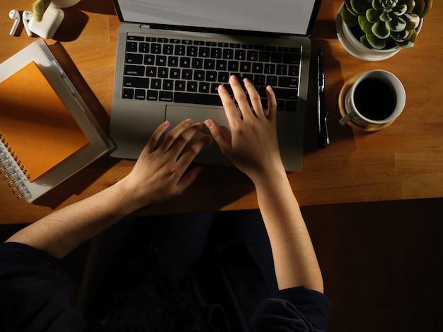 Ujęcie kobiece ręki wpisując na laptopie na drewnianym stole z papeterii i doniczki