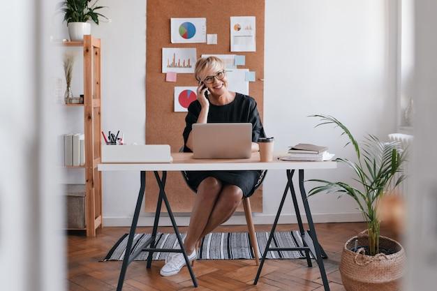 Ujęcie kobiety biznesu w czarnej sukni rozmawia przez telefon