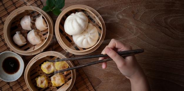 Ujęcie kobiety jedzącej chińską pierożek na parze i bułkę wieprzową na parze w bambusowym parowcu