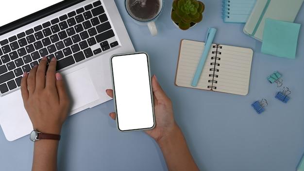 Ujęcie kobiety trzymającej inteligentny telefon i pracującej na komputerze przenośnym na pastelowej niebieskiej powierzchni