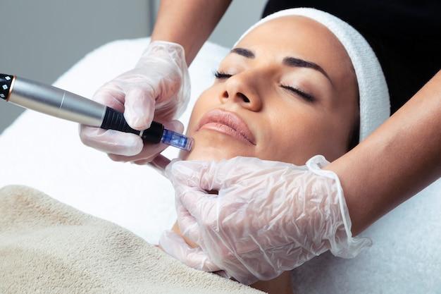 Ujęcie kosmetologa wykonującego zastrzyk mezoterapii z dermapenem na twarz w celu odmłodzenia w centrum spa.