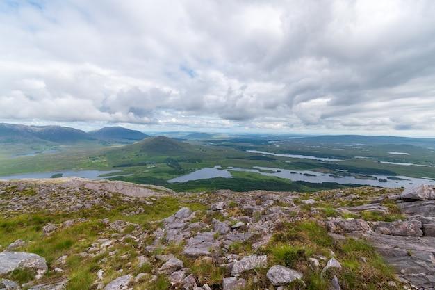 Ujęcie krajobrazu gór i jeziora przed zachmurzonym niebie, connemara, irlandia.