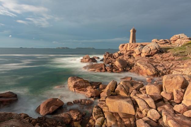 Ujęcie latarni morskiej stojącej nad brzegiem morza pod zachmurzonym niebem