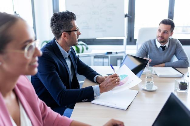 Ujęcie ludzi biznesu omawianie razem w sali konferencyjnej podczas spotkania w biurze.