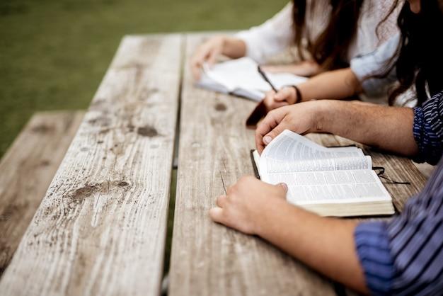 Ujęcie ludzi siedzących obok siebie i czytających biblię