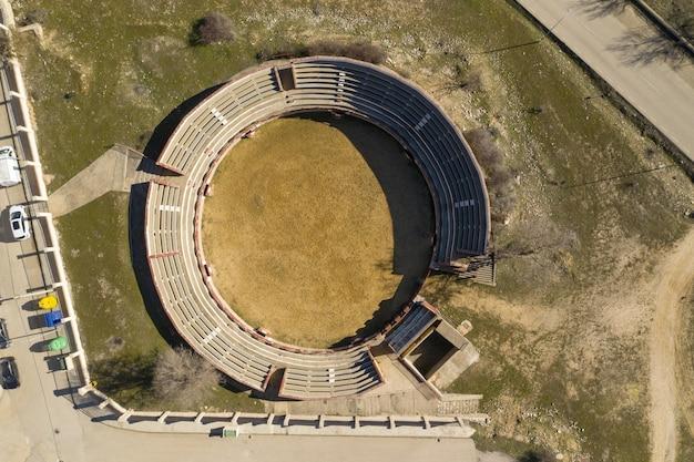 Ujęcie małego kamiennego stadionu na trawiastym podwórku