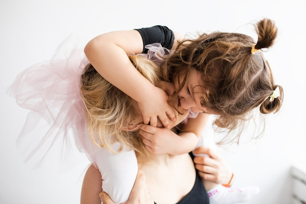 Ujęcie matki całującej swoją córeczkę w domu, mama i córeczka w wieku 4 lat przytulają się i całują, nierozpoznawalni ludzie