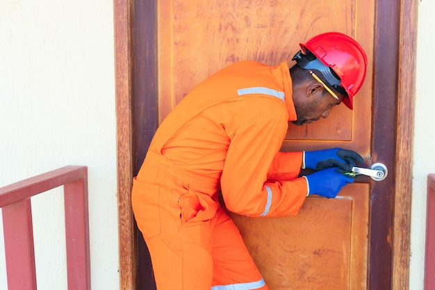 Ujęcie mężczyzny naprawiającego drzwi w domu