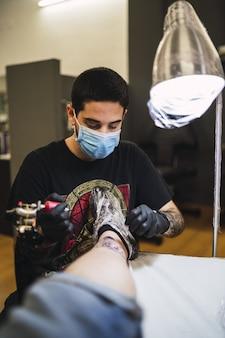 Ujęcie mężczyzny tatuatora tatuującego nogę swojego klienta
