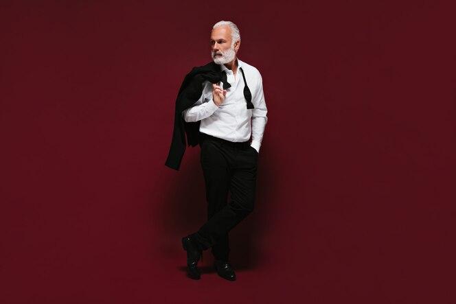 ujęcie mężczyzny w białej koszuli i spodniach na izolowanej ścianie