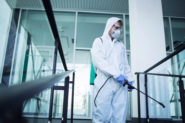 Ujęcie mężczyzny w białym kombinezonie chroniącym przed chemikaliami, wykonującego dezynfekcję miejsc publicznych w celu powstrzymania rozprzestrzeniania wysoce zaraźliwego wirusa koronowego
