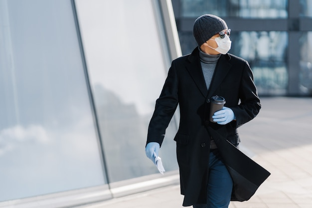 Ujęcie młodego człowieka pozuje na zewnątrz na ulicy, wygląda na bok, nosi okulary przeciwsłoneczne, gumowe rękawiczki, maskę medyczną podczas wybuchu koronawirusa, pije gorący napój, próbuje uniknąć miejsc publicznych podczas epidemii