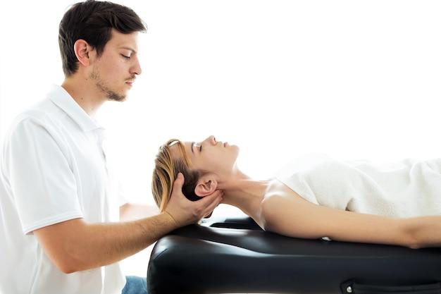 Ujęcie młodego fizjoterapeuty wykonującego leczenie szyi pacjentowi w sali fizjoterapii. koncepcja rehabilitacji, masażu leczniczego i terapii manualnej.