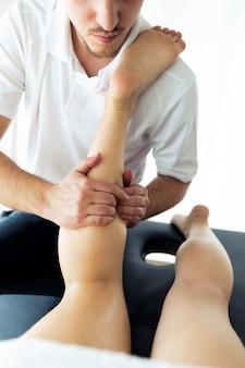 Ujęcie młodego fizjoterapeuty wykonującego zabieg na nogi pacjentowi w sali fizjoterapii. koncepcja rehabilitacji, masażu leczniczego i terapii manualnej.