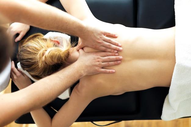 Ujęcie młodego fizjoterapeuty wykonującego zabieg na plecy pacjenta w sali fizjoterapii. koncepcja rehabilitacji, masażu leczniczego i terapii manualnej.