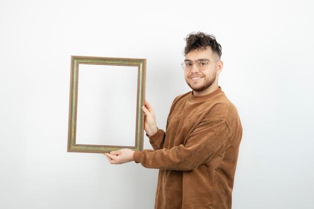 Ujęcie młodego modelu płci męskiej z pustą ramką stojącej nad białą ścianą.