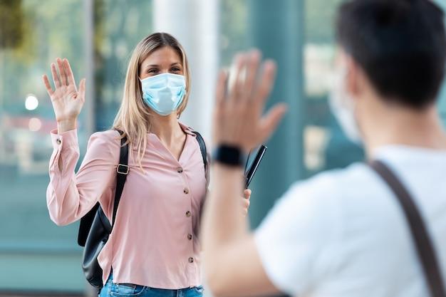 Ujęcie młodej blond studentki noszącej maskę chirurgiczną i machając ręką na powitanie jej przyjaciela w kampusie uniwersyteckim w epidemii covid19. dystans społeczny i nowa koncepcja normalności.
