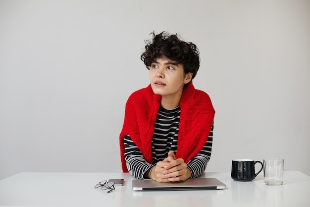 Ujęcie młodej dość krótkiej, kręconej brunetki kobiety z naturalnym makijażem składane usta na swoim laptopie, siedząc na białym tle, patrząc w zamyśleniu na bok ze spokojną twarzą